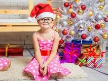 Mädchen im roten Hut und in den lustigen runden Gläsern sitzt auf der Matte an den Weihnachtsbäumen Stockfotos