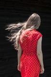 Mädchen im roten Kleid auf dem schwarzen Wandhintergrund Stockbilder