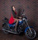 Mädchen im roten Kleid auf einem Motorrad Lizenzfreie Stockfotos