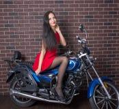 Mädchen im roten Kleid auf einem Motorrad Stockbild