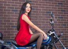 Mädchen im roten Kleid auf einem Motorrad Lizenzfreie Stockfotografie