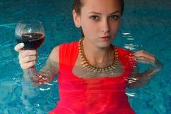 Mädchen im roten Kleid, das mit Glas Wein herein steht Stockbilder
