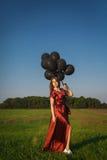 Mädchen im roten Kleid mit den schwarzen Ballonen, die auf einem Gebiet stehen Stockfoto