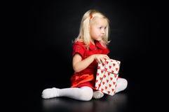 Mädchen im roten Kleid mit Geschenk stockfotos