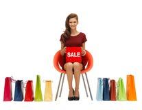 Mädchen im roten Kleid mit Schuhen, Taschen- und Verkaufszeichen Lizenzfreie Stockbilder