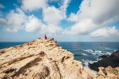 Mädchen im roten Kleid unter Felsen und Klippen entlang der Küste von Algarve stockfotos