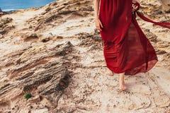 Mädchen im roten Kleid unter Felsen und Klippen entlang der Küste von Algarve Lizenzfreies Stockfoto