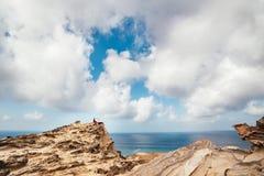 Mädchen im roten Kleid unter Felsen und Klippen entlang der Küste von Algarve stockfoto