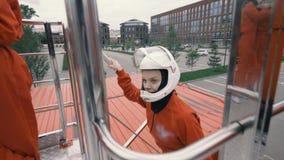 Mädchen im roten Overall und im Schutzhelm steigt oben Treppe stockfoto