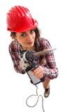 Mädchen im roten Sturzhelm mit dem Bohrgerät, das oben schaut Lizenzfreies Stockfoto