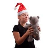 Mädchen im roten Weihnachtshut und -bären Stockbilder