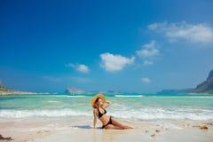 Mädchen im schwarzen Bikini und mit Hut auf Balos-Strand stockfoto