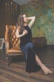 Mädchen im schwarzen Kleid, das auf Stuhl sitzt Lizenzfreies Stockfoto