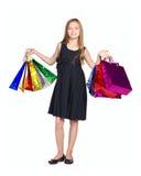 Mädchen im schwarzen Kleid mit vielen färben Beutel Lizenzfreie Stockfotos
