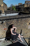 Mädchen im schwarzen Tupfenkleid, das auf dem Balkon sitzt stockbild