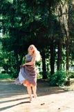 Mädchen im Schwarzweiss-Kleid in der Natur auf einem Hintergrund von Kiefern Stockfotos