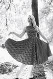 Mädchen im Schwarzweiss-Kleid in der Natur auf einem Hintergrund von Kiefern Stockfoto