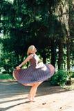 Mädchen im Schwarzweiss-Kleid in der Natur auf einem Hintergrund von Kiefern Lizenzfreies Stockbild