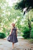 Mädchen im Schwarzweiss-Kleid in der Natur auf einem Hintergrund von Kiefern Lizenzfreies Stockfoto