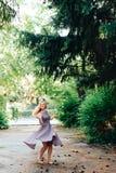 Mädchen im Schwarzweiss-Kleid in der Natur auf einem Hintergrund von Kiefern Lizenzfreie Stockfotos