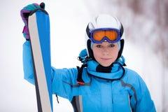 Mädchen im Skianzug mit Skis Stockbilder