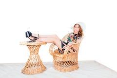 Mädchen im Sommerhut lokalisiert auf geflochtenem Stuhl Stockbild