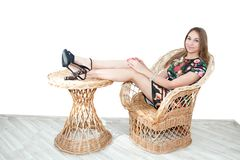 Mädchen im Sommerhut lokalisiert auf geflochtenem Stuhl Stockfotografie