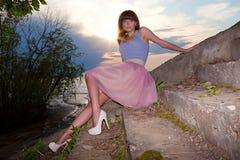 Mädchen im Sommerkleid auf schmutziger konkreter Treppe Lizenzfreie Stockfotos