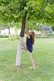 Mädchen im Sommerversuch zum Springen auf Baum Lizenzfreies Stockbild