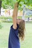 Mädchen im Sommerversuch zum Springen auf Baum Lizenzfreie Stockbilder