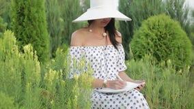 Mädchen im Sonnenhut und -kleid unter grünen Bäumen und Gras stock video footage