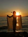 Mädchen im Sonnenuntergang mit Schal und Vögeln Stockfoto