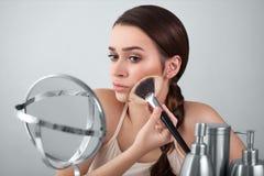 Mädchen im Spiegel setzt Make-upbürste Stockbild