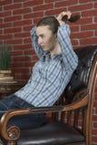 Mädchen im Stuhl richtet ihre Frisur gerade Stockbild