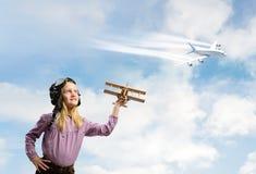 Mädchen im SturzhelmVersuchsspielen mit einem Spielzeugflugzeug Lizenzfreie Stockfotografie