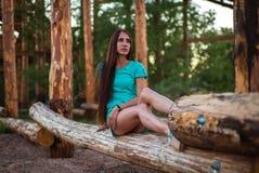 Mädchen im Türkiskurzschlusskleid, das auf einem Baumklotz sitzt stockfoto