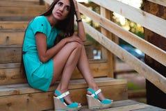 Mädchen im Türkiskurzschlusskleid, das auf einem Baumklotz sitzt stockbild