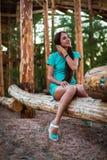 Mädchen im Türkiskurzschlusskleid, das auf einem Baumklotz sitzt stockfotos