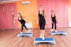 Mädchen im Training mit Dummköpfen und aeroben Schritten Stockfotografie