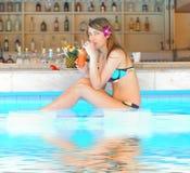 Mädchen im tropischen Poolstab Stockbild