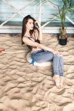 Mädchen im Urlaub, das auf dem Sand sitzt lizenzfreies stockbild