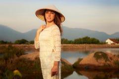 Mädchen im vietnamesischen Hut gegen Seen bringen Berge unter Stockfoto