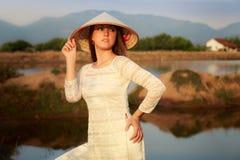 Mädchen im vietnamesischen Hut gegen Seen schaukelt Reflexion Stockbilder