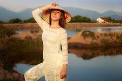 Mädchen im vietnamesischen Hut gegen Seen schaukelt Reflexion Stockfotografie