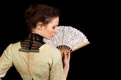 Mädchen im viktorianischen Kleid mit dem Fan gesehen von der Rückseite stockfoto