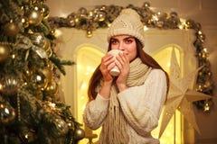 Mädchen im warmen Kleidungstrinkbecherkaffee zu Hause im neuen Jahr stockfoto