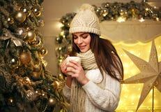 Mädchen im warmen Kleidungstrinkbecherkaffee zu Hause im neuen Jahr lizenzfreie stockfotos