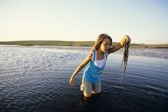 Mädchen im Wasser mit Anlagen lizenzfreie stockfotos