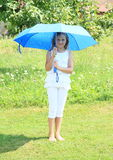 Mädchen im Weiß mit blauem Regenschirm Stockfoto