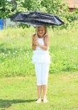 Mädchen im Weiß mit defektem blauem Regenschirm Lizenzfreie Stockfotos